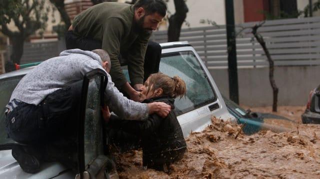 Zwei Männer auf einem Auto ziehen eine Frau aus den Fluten auf einer Strasse.