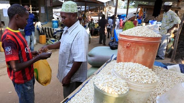 Ein Mann kauft einem Veräufer Mais ab.
