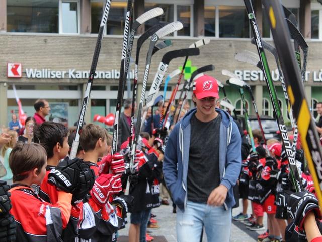 Buben mit Eishockeystocks bilden eine Gasse für den Spieler.