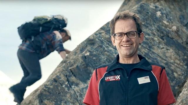 Ein Sportartikelverkäufer im Vordergrund, im Hintergrund ein Bergsteiger