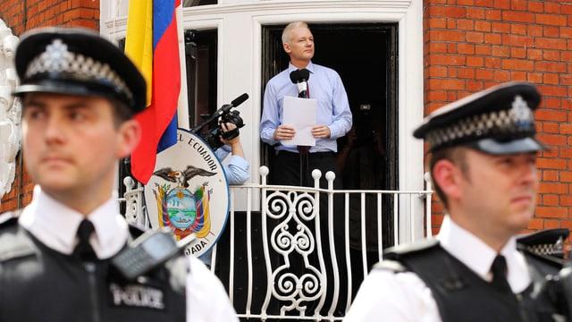 Julian Assange auf dem Balkon der Botschaft Ecuadors in London, im Vordergrund Polizisten.