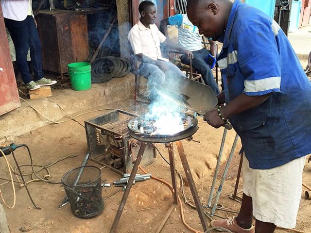 Der Ortsmechaniker in Ifakara schweisst die Speichen ans Rad, über das die Schnur der Handpumpe läuft.