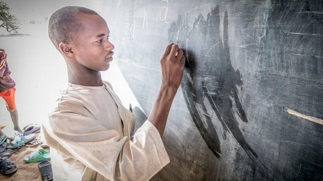 Ein Lehrer steht an einer Wandtafel und schreibt etwas darauf