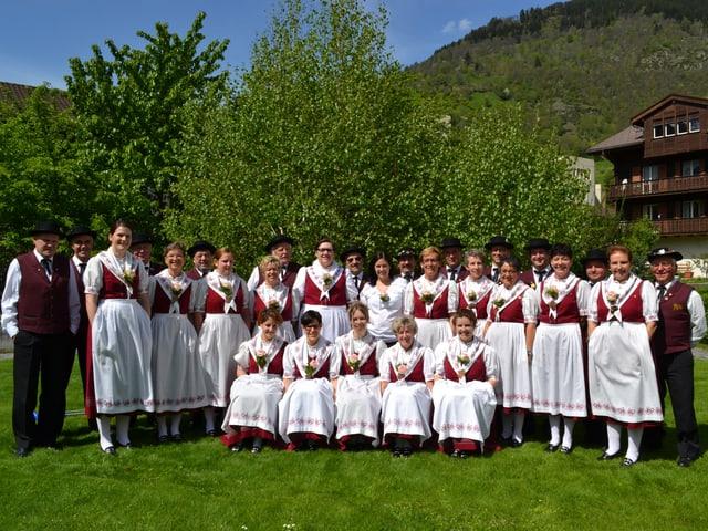 Eine grosse Gruppe von Jodlerinnen und Jodlern in rot-weissen Trachten auf einer grünen Wiese in den Bergen.