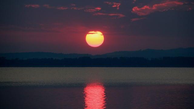Sonnenaufgang am Murtensee mit rotspiegelnder Sonne auf dem See