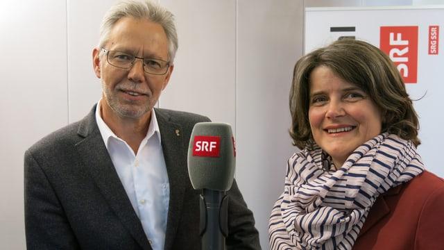 Peter Riebli und Kathrin Schweizer stehen hinter einem Mikrofon.