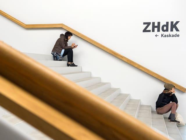 """Zwei Studentinnen sitzen auf der Treppe. An der Wand steht """"ZHdK"""" und """"Kaskade"""" mit einem Pfeil, der die Richtung weist."""