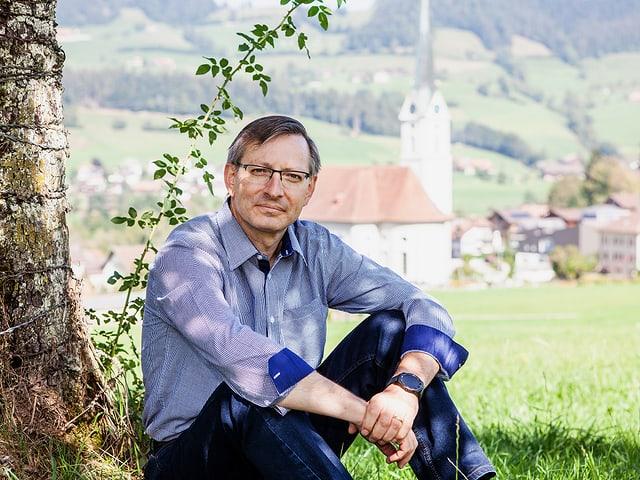 Urs Corradini sitzt neben einem Baum. Im Hintergrund ist eine Kirche zu sehen.