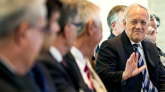 Johann Schneider-Ammann sitzt in einer Reihe mit anderen Männern, er gestikuliert mit der rechten Hand.