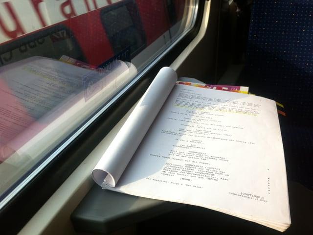 Ein Drehbuch liegt auf dem Tisch eines Zugabteils.