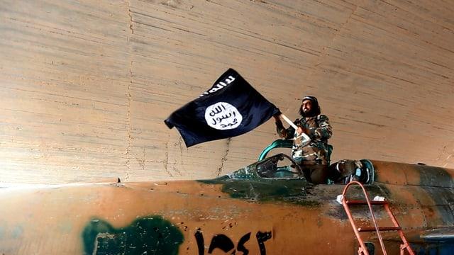 Mann steht in einem Militärfluzeug mit einer Fahne in der Hand.
