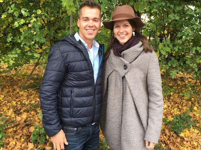 Ein junge Mann und eine junge Frau auf einer Wiese mit Herbstlaub.