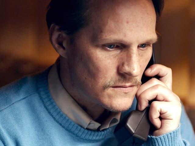 Ein Mann am Telefon, er schaut ernst.