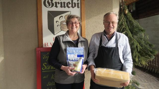 Ein Mann und eine Frau stehen vor dem Käseladen. Er hat einen Laib in der Hand, sie präsentiert ein Fondue.
