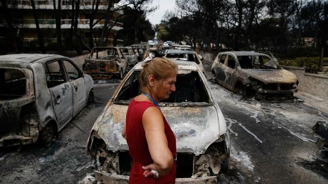 Frau steht vor verbrannten Autos, die durch ein Wildfeuer zerstört wurden