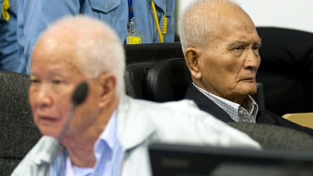 Zwei alte Männer, die beiden Angeklagten, sitzen regungslos im Gerichtssaal.