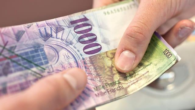 Eine Hand hält eine Tausendernote.