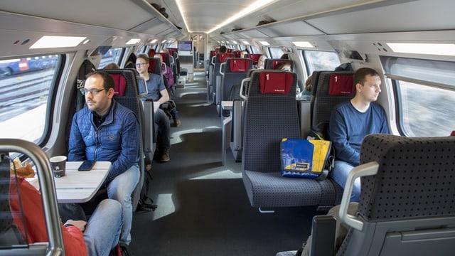 Reisende in einem Erstklass-Abteil im Zug.