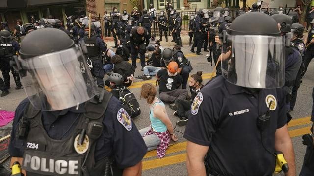 Demonstranten mit gefesselten Händen sitzen am Boden