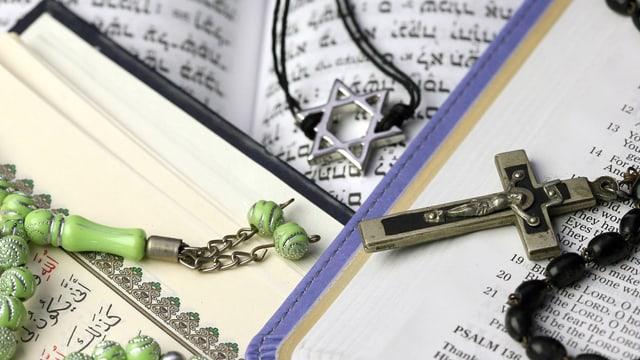 Drei Bücher liegen übereinander, darauf die Symbole der drei Religionen Christentum, Judentum und Islam.