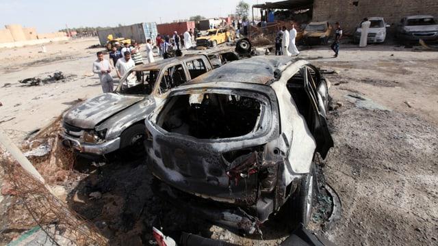 Zwei ausgebrannte Autos, darum herum Zivilisten
