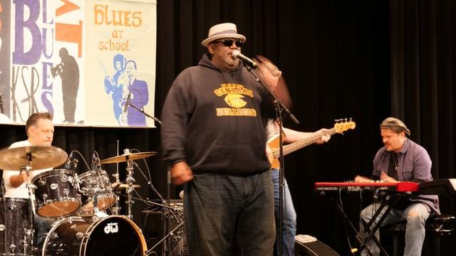 Musiker mit Hut am Mikrophon, hinter ihm die Band