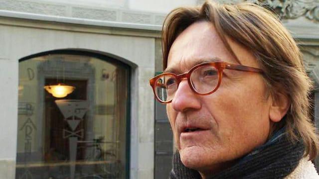 Die Fotografie zeigt einen Mann mittleren Alters mit Hornbrille und halblangen, hellbraunen Haaren.