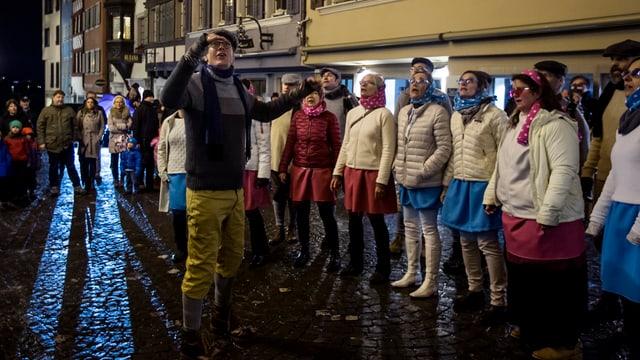 Eine Gesangsgruppe singt vor einem Haus