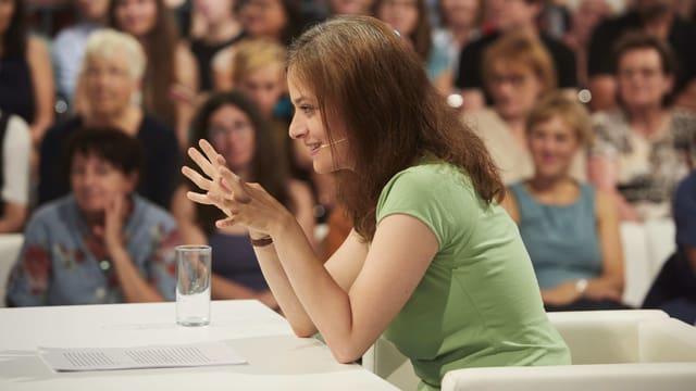 Frau in grünem Shirt sitzt vor Publikum an einem Tisch
