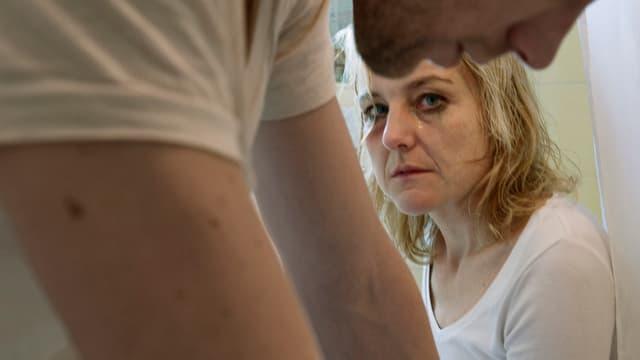 Frau mit Tränen in den Augen, vor ihr das Profil eines Mannes.