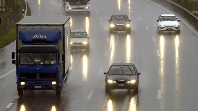 Eine nasse Autobahn mit verschiedenen Fahrzeugen, die mit Licht am Tag fahren.