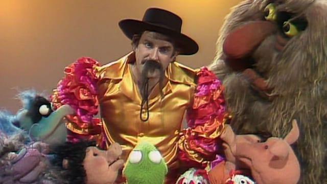 John Cleese umgeben von den Muppets. Er trägt ein Mexikaner-Kostüm.