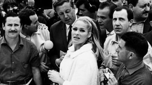 Eine Frau umringt von Reportern und Schaulustigen.