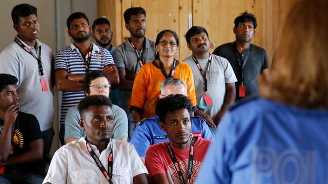 Eine Gruppe Asylsuchender sitzt vor einer Polizistin, welche ihnen etwas erklärt.