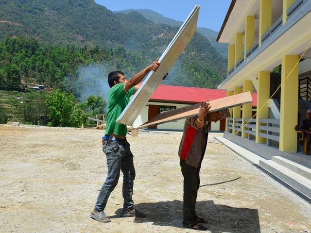 Zwei Arbeiter mit Türen vor dem gelben Schulgebäude.