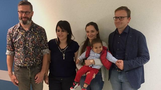 Eine Gruppe von Menschen, eine Frau hält einen kleinen Jungen im Arm.