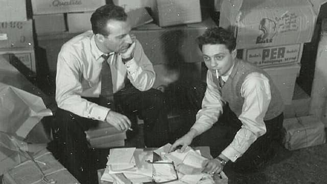 Die Glückskette-Gründer Roger Nordmann (links) und der Entertainer Jack Rollan knien 1946 vor einer Kiste mit Hilfsgütern
