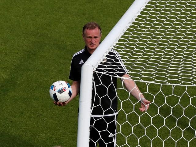 Michael O'Neill schreitet mit dem Ball in den Händen über den Rasen.