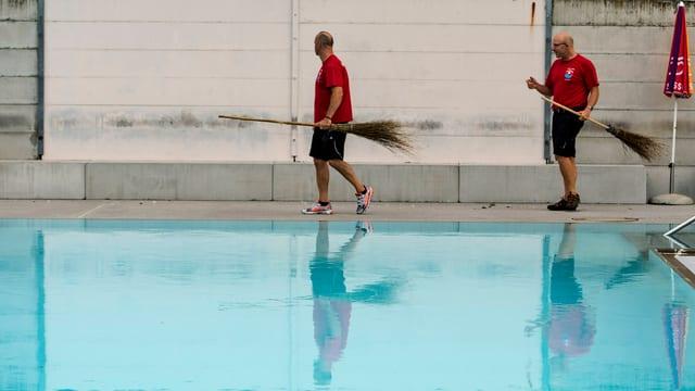 Zwei Bademeister mit Besen in der Hand vor einem Pool