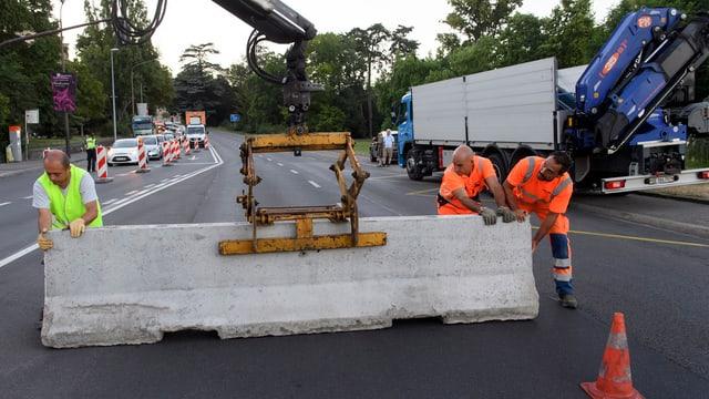 Bauarbeiter stellen in Genf mithilfe eines Krans einen Betonblock auf.