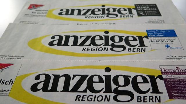 Vier Zeitungen vom Anzeiger Region Bern liegen aufgereiht auf einem weissen Tisch.