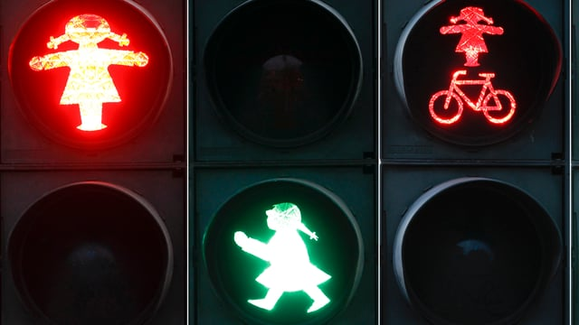 Ampel für Fussgänger und Velofahrer: rote und grüne Frauenfiguren regeln den Verkehr.