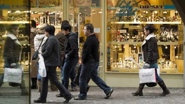 Menschen gehen auf der Strasse an einem Schaufenster mit Uhrenauslagen vorbei