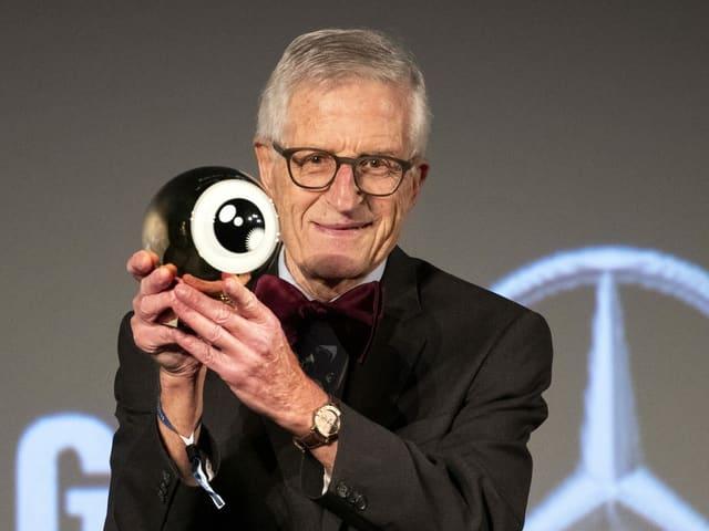 Ein älterer Mann im Anzug hält einen Preis in Form eines Auges in der Hand und schaut in die Kamera.
