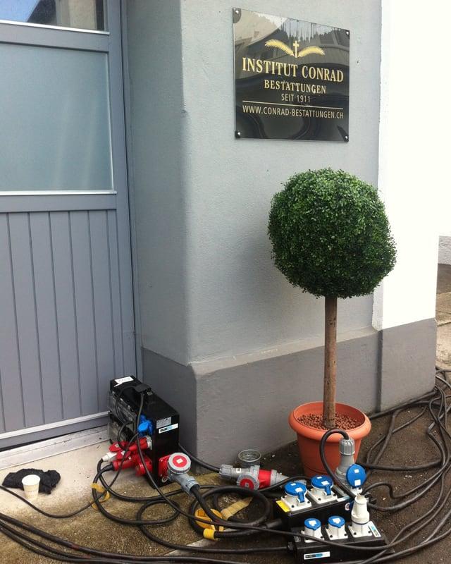 """Eingang zu einem Inbdustriegebäude, neben der Tür ein Schild """"Institut Conrad"""", am Boden viele Kabel."""