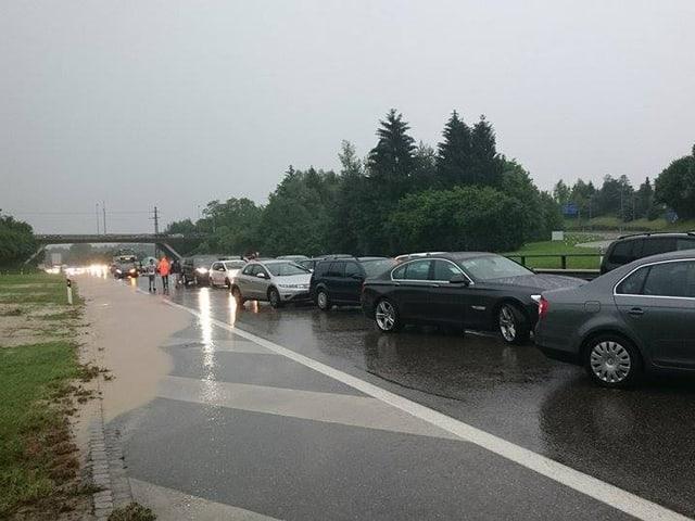 Autos stauen sich auf der Autobahn im Regen.