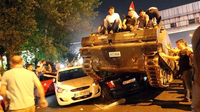 Menschen fahren mit Panzer über Autos