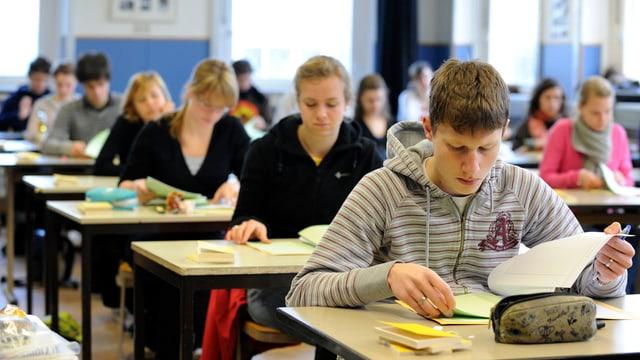 Jugendliche Schüler an Tischen mit Heften am Prüfung schreiben