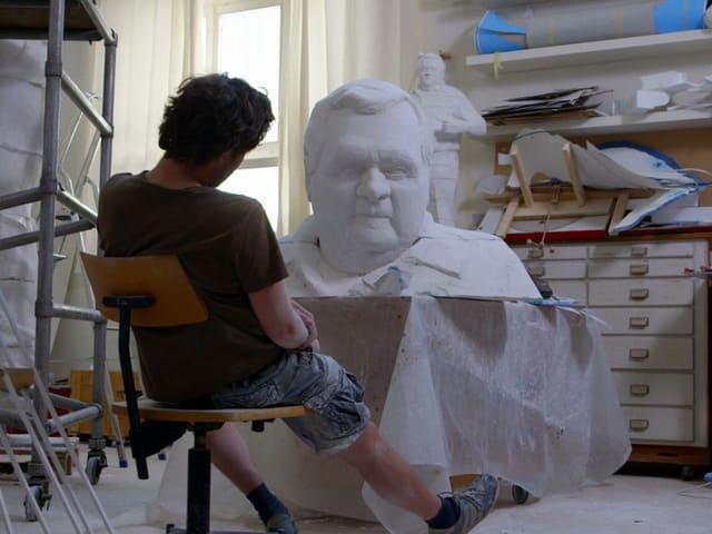 Christoph Fischer in seinem Atelier vor der Büste seines geplanten Statue namens Heinz.