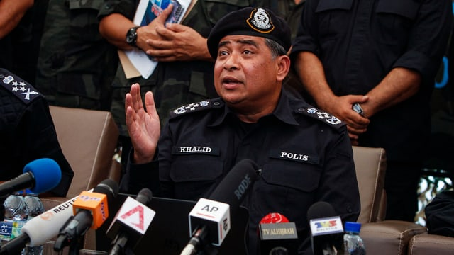 Il schef da la polizia da la Malaisia che discurra envers las medias. Davant el èn blers microfons.
